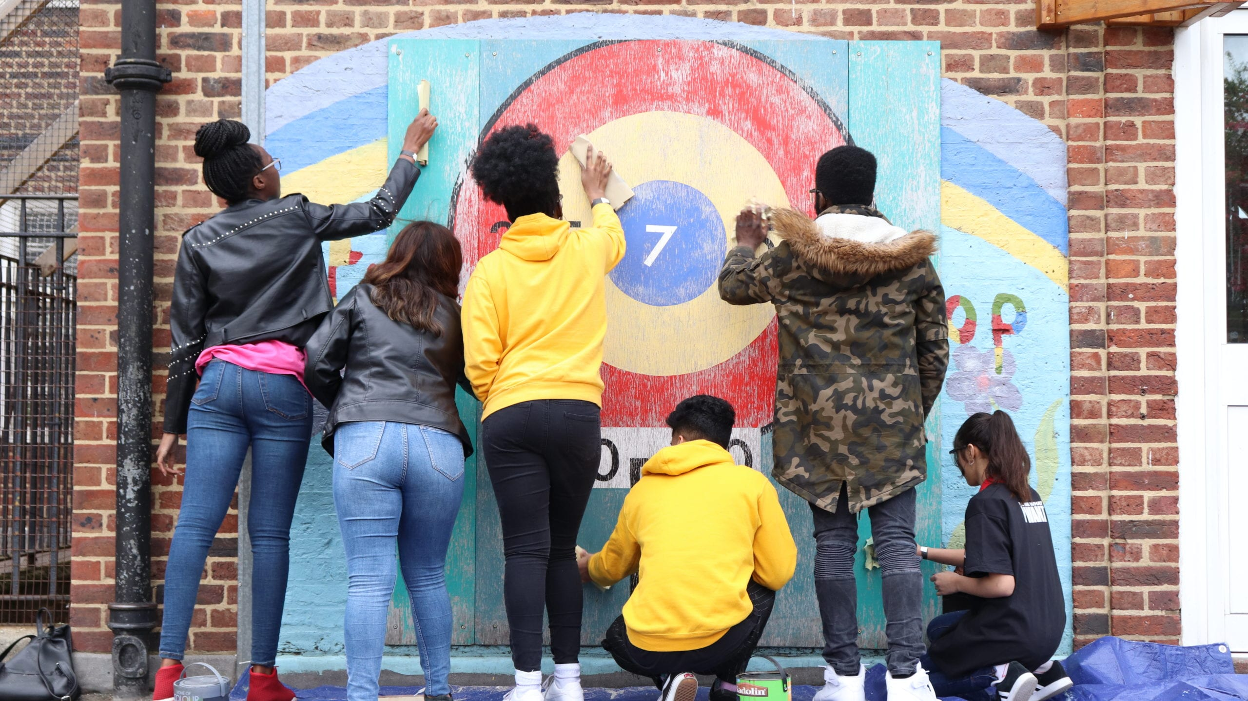 Young people getting involved in social action and painting a community wall.